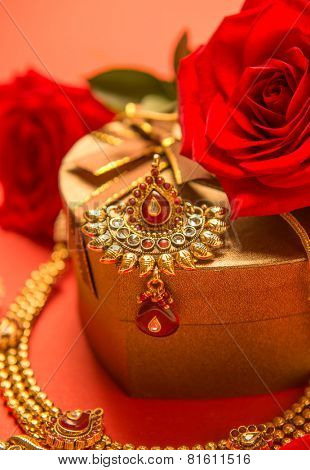 Close up of a golden Indian ornament which is to be worn on forehead by women. An antique style jewelry arranged with red roses and a gift box.