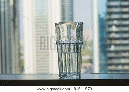 A half filled glass of water placed against window with skyline background.