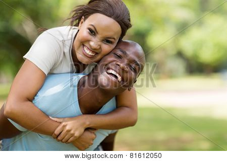 attractive young black couple piggybacking outdoors