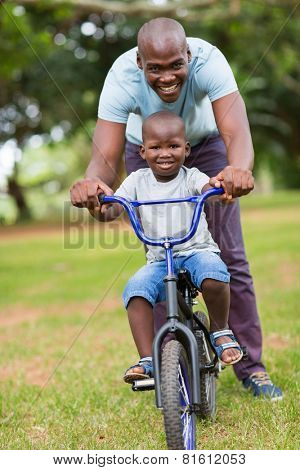 cheerful african american man teaching son to ride a bicycle at the park