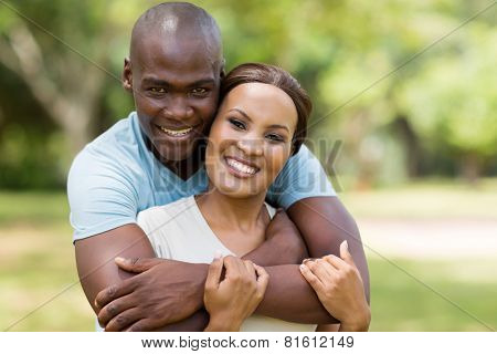 good looking african man hugging girlfriend outdoors
