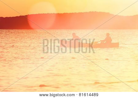 Time Together, silhouette of couple canoeing on a lake. Instagram effect