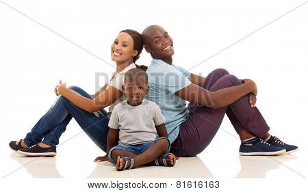 happy young afro american family sitting on the floor isolated on white background