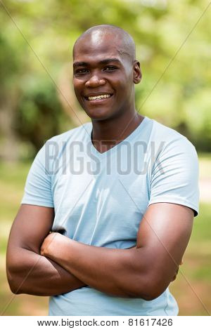 good looking young african man with arms crossed outdoors