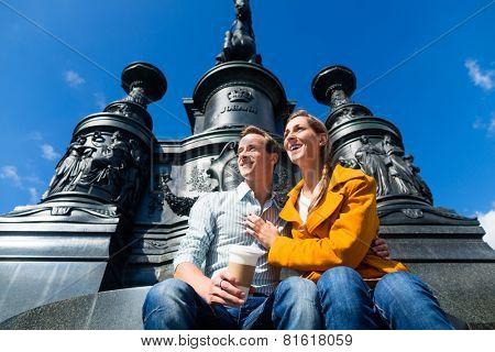 Tourist couple sitting in Dresden Theaterplatz in front of statue