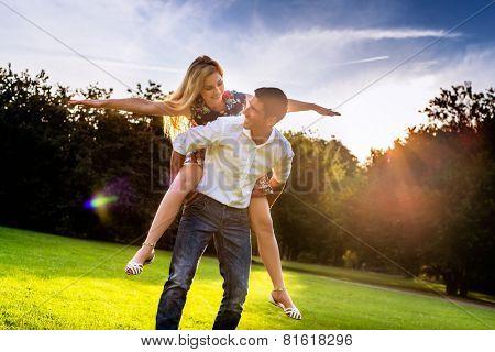 Man carrying girl piggyback in summer in backlit sunset scene