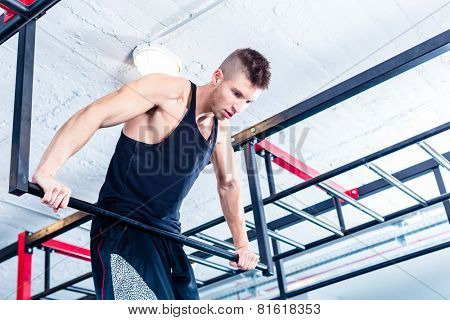 Man at freestyle Calisthenics training in gym on frame