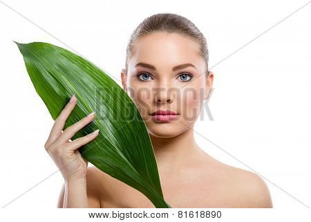 Beauty portrait,  pure beauty model with perfect fresh skin holding green leaf next  face