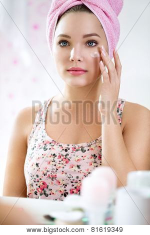 Young girl in bathroom front of mirror putting cream, skincare