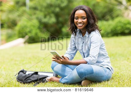 portrait of african college girl sitting at the park