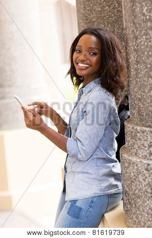 happy female african uni student using smart phone