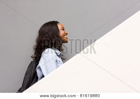 side view of african american college student walking up the stairs