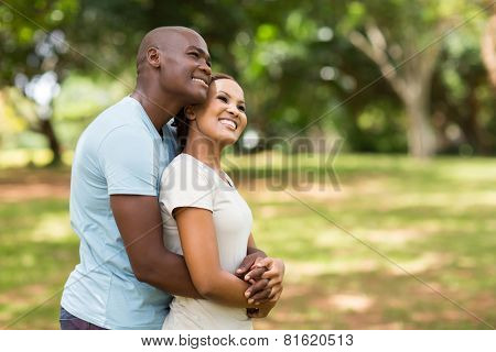 cute young african couple daydreaming in forest