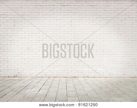 room with white bricks wall and gray floor