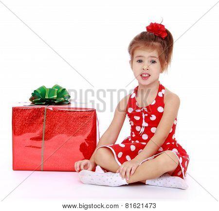 Adorable little girl sitting on the floor folding legs in Turkis
