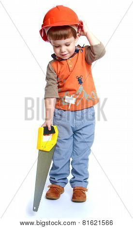 Little boy holding a hacksaw on wood.