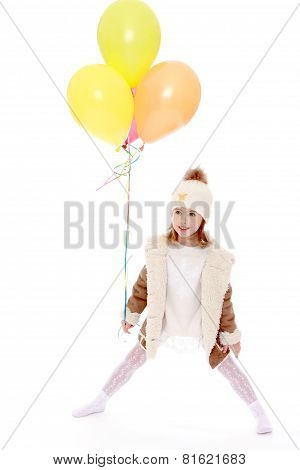 Little girl in hat and coat holding a balloons.