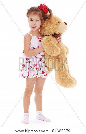 Adorable little girl teddy bear in hand .