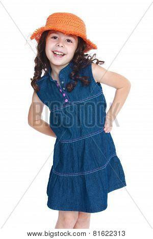 Beautiful little girl in a denim dress and orange hat.