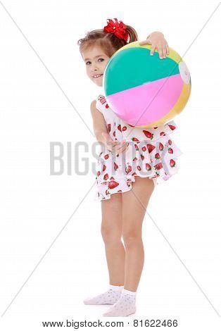 Beautiful little girl with big inflatable ball.