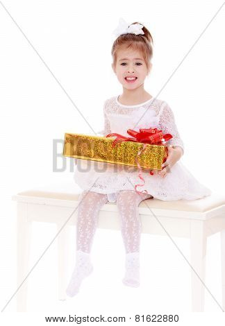 Adorable little girl is sitting on a white couch to keep in the