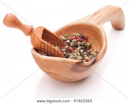 Black, green and pink pepper peppercorn mix in wooden spoon isolated on white background cutout
