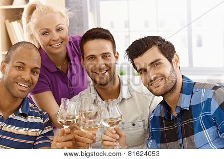 Closeup photo of celebrating friends smiling happy, clinking glasses, looking at camera.