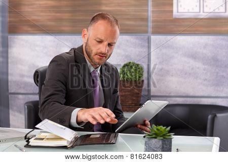 Businessman in trouble between tablet computer and personal organizer, sitting in office.