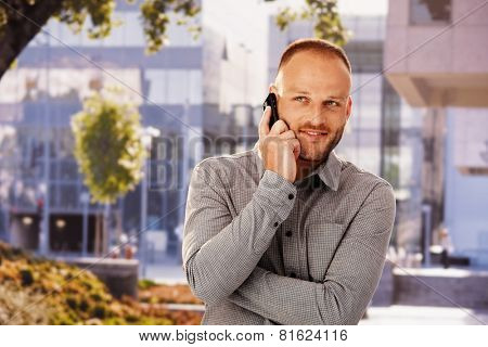 Smiling young man talking on mobilephone outdoors, looking away.