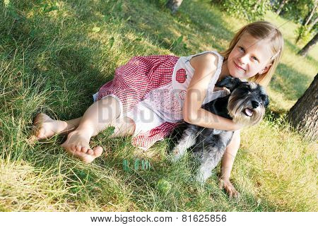 Cute Little Girl Lying On The Grass In The Park, Beside Her Dog