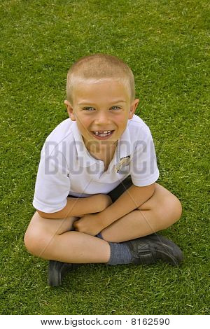 Cute Six Seven Year Old Schoolboy Sitting On The Grass