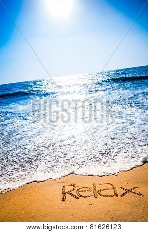 The Word Relax Written Into The Sand On A Beach