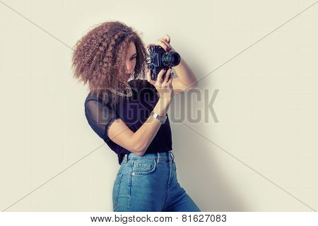 beautiful young girl hipster makes the images, photographs on the camera in jeans and a black t-shir