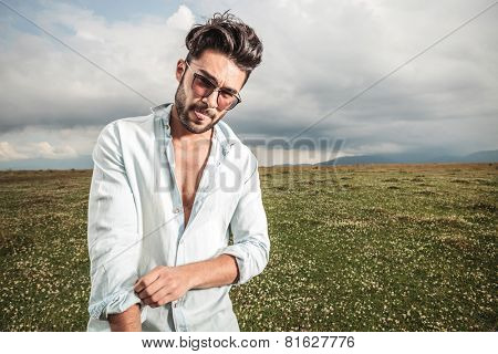Young fashion man fixing his sleeve while showing his tongue, outdoor picture.