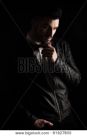 Young business man looking down while holding his hand to his chin, on dark studio background.