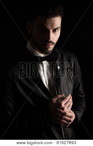 Handsome business man holding his hands together while looking at the camera, on dark studio background.
