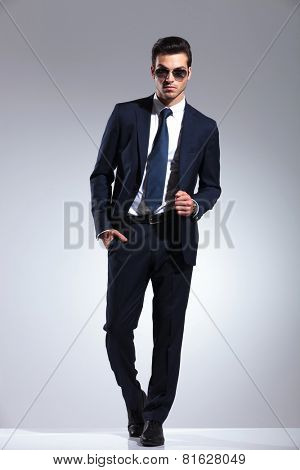 Full length picture of a elegant business man posing on grey studio background, holding one hand in his pocket while pulling his jacket.