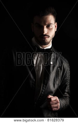 Portrait of a young business man wearing a leather jacket, looking away from the camera, thinking.