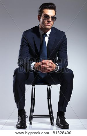 Young business man resting on a stool, looking away from the camera while holding his hands together.