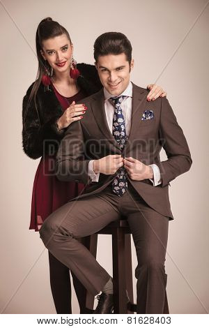 Handsome young fashion man sitting on a stool while closing his jacket. His girlfriend is standing behind him with her hands on his shoulders.