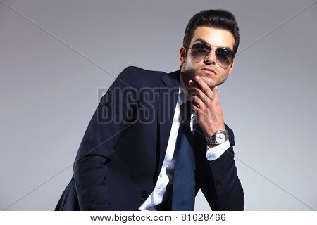 Young business man looking up while holding his hand to his chin, thinking of something.