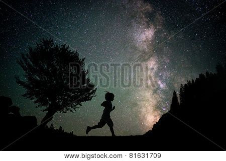 Happy child running silhouette with Milky Way and beautiful night sky full of stars in background