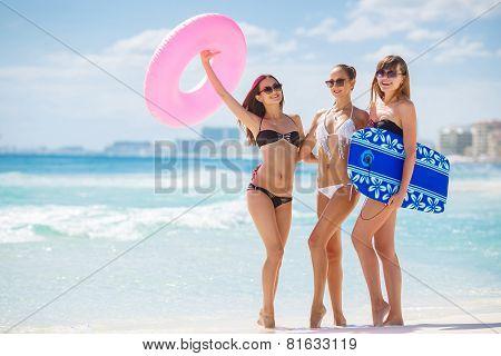Three slim woman in bikini with a lifeline, having fun near the ocean.