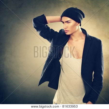 Fashion young model man portrait. Handsome Guy wearing hat. Vogue style image of stylish young man. Studio fashion portrait.