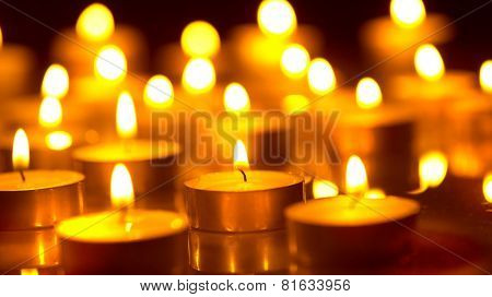 Candles light background. Candle flame at night. Holiday candles close up.m Abstract glowing background