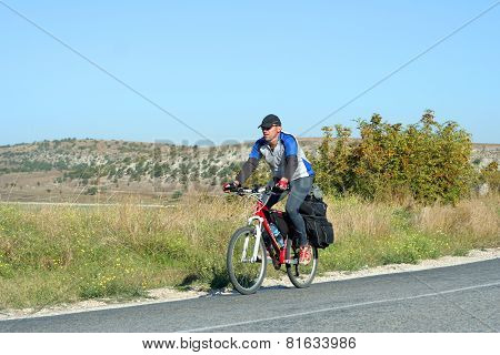 A young male riding a mountain bike outdoor.