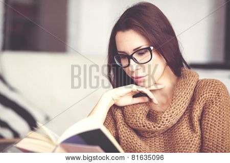 Young woman wearing warm sweater relaxing on cozy chair and reading book at home