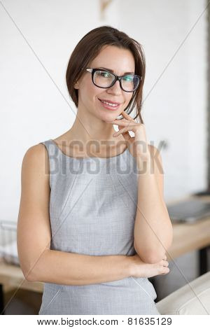 30 years old young woman wearing glasses standing indoors and looking at camera