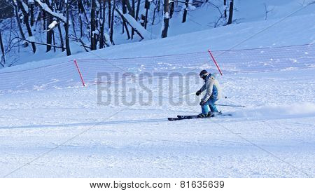A Man In A Multicolored Jacket Riding A Snowboard