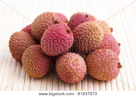 Lots of litchis grouped on bamboo mat
